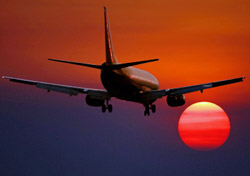 Airplane flying towards red sky (Photo: Timothy Goodwin/iStockphoto)