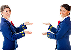 Two Flight Attendants Smiling at Camera and Gesturing (Photo: Shutterstock)
