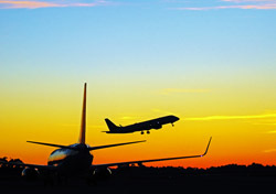 Air: Two Planes - One Parked, Another Taking Off (Photo: Shutterstock/jose marques lopes)