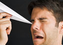 Man getting poked in the eye by paper plane.
