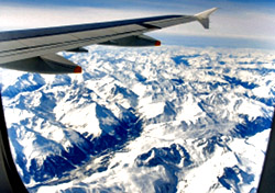 Airplane Wing Over Snow-Covered Mountains (Photo: iStockphoto/Adrian Assalve)