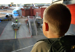 Boy looking at an airplane through terminal window (Photo: Mikael Damkier/iStockphoto)