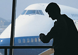 Airport: Man Looking at Watch (Photo: Thinkstock/Comstock)