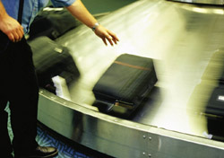 Man reaching for suitcase on baggage carousal (Photo: Index Open)