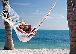 Woman relaxing in hammock between two palm trees (Photo: Christian Wheatley/iStockphoto)