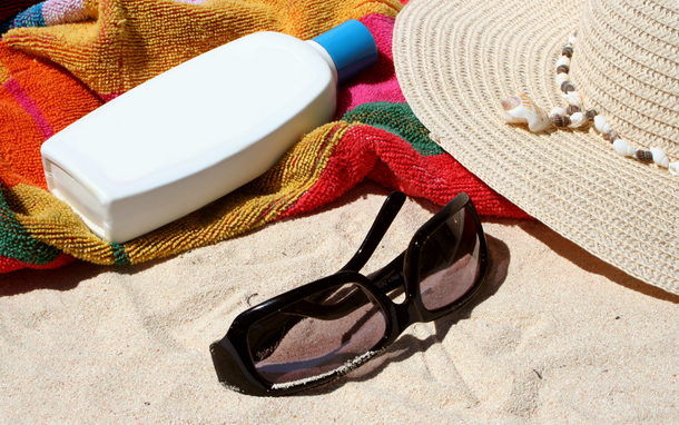 Sunglasses, Lotion, and Hat on Sand (Photo: Graca Victoria/Shutterstock.com)