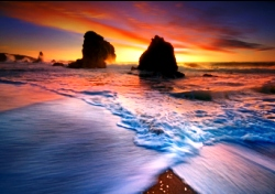 Beach With Rocks and Waves at Colorful Sunset (Photo: Thinktock/iStockphoto)