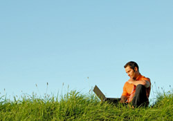 Man looking at laptop in Meadow (Photo: iStockPhoto/Kemter)
