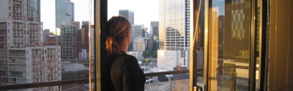 Girl Standing at City Window (Photo: iStockPhoto/Scott Espie)