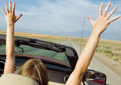 Couple in Car With Raised Arms (Photo: Thinkstock/Jupiterimages)