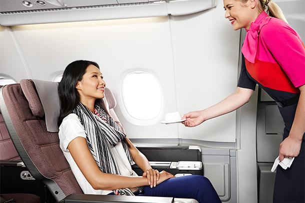 Passenger Being Served Tea in Qantas Premium Economy Seating (Photo: Qantas)
