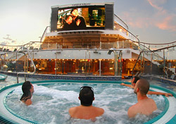 "Many cruise ships have indoor movie theaters, but <a href=""http://www.princess.com/index.html"" target=""_blank"">Princess</a> and <a href=""http://www.carnival.com/"" target=""_blank"">Carnival</a> have placed giant LED screens on their pool decks. Cruisers can lay out on a deck chair, margarita in hand, and watch rock concerts, sports events, and recently released movies. With Princess' Movie Under the Stars program, guests receive blankets and popcorn as they snuggle together to catch a flick. (Photo: Carnival)"