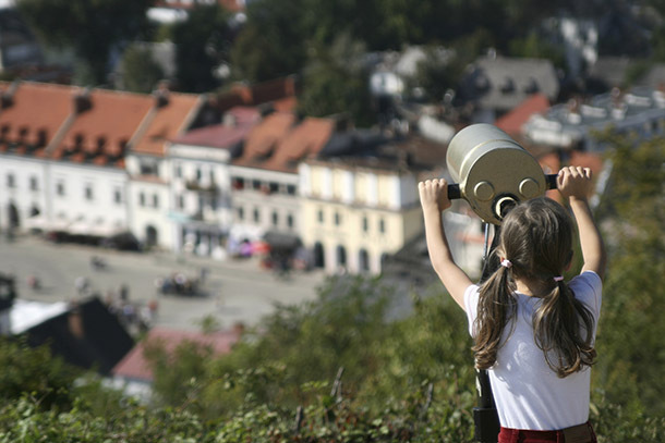 Europe: Girl Observing Old Town Via Telescope (Photo: Thinkstock/iStockphoto)