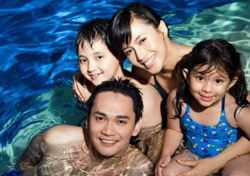 Family with two children in pool (Photo: iStockPhoto/Christian Michael)