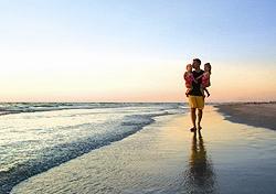 Father and twins on the beach on Anna Maria Island (Photo: Bradenton Area CVB)