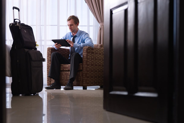 Hotel: Business Man with Luggage, Using Tablet (Photo: Shutterstock/Diego Cervo)