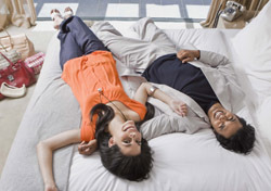 Hotel: Couple Laying on Bed (Photo: Thinkstock/Jupiterimages)