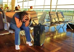 Woman Waiting, Holding Head in Hands at Airport (Photo: Patryk Kosmider/Shutterstock)