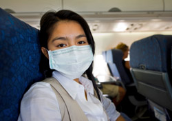 Woman wearing a mask on a plane (Photo: iStockphoto/Marcel Braendli)