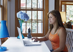 Woman in orange using laptop (Photo: Index Open)