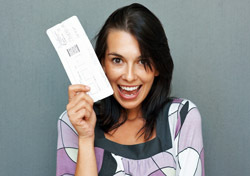 Woman: Excited with Ticket in Hand (Photo: Shutterstock/Yuri Arcurs)