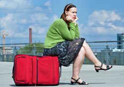 Woman: Waiting, Sitting on Red Suitcase (Photo: Shutterstock/SFC)