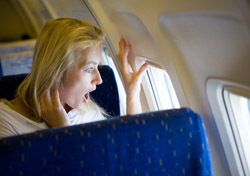 Air: Woman Frightened Looking Out Plane Window (Photo: Thinkstock/iStockphoto)