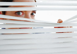 Woman: Peeking Through Blinds (Photo: Thinkstock/Wavebreak Media)