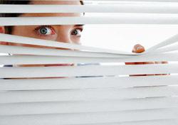 Woman: Peeking Through Blinds (Photo: Thinkstock/Wavebreak Media)